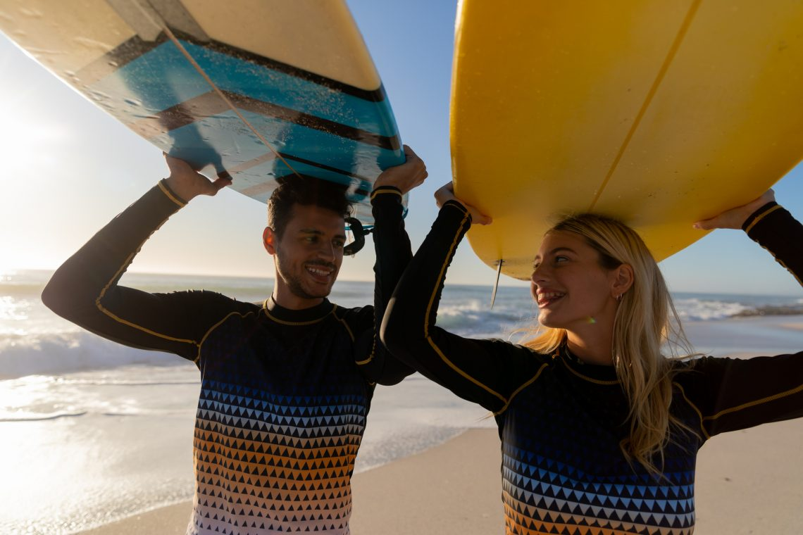 Caucasian couple enjoying time at the beach on a sunny day, holding surfboards above their heads with sea in the background