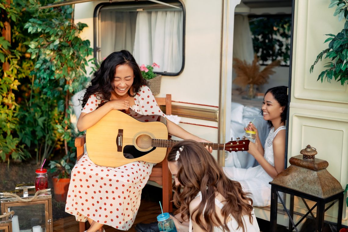 Laughing happy women with guitar have fun together outdoors near