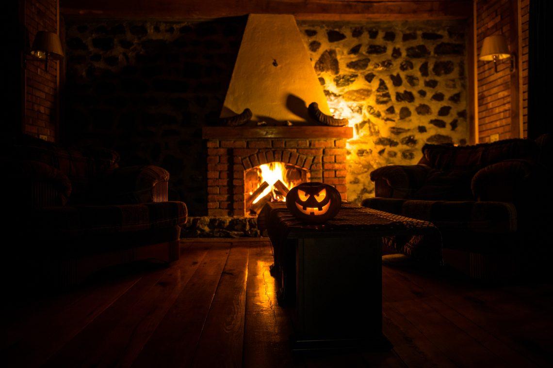 Creepy halloween pumpkin near a fireplace. Fire on the background.