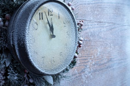 Christmas clock over snow wooden background.