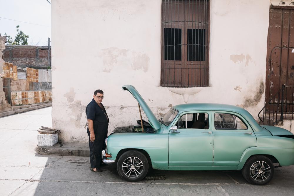 Фото мужчины возле зеленой машины