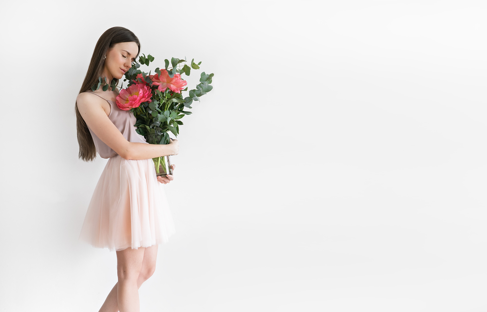 Beautiful girl with peonies in hands on a light background