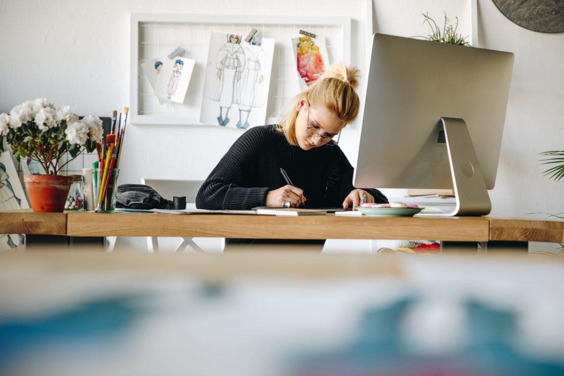 женщина-дизайнер работает за столом с компьютером фото