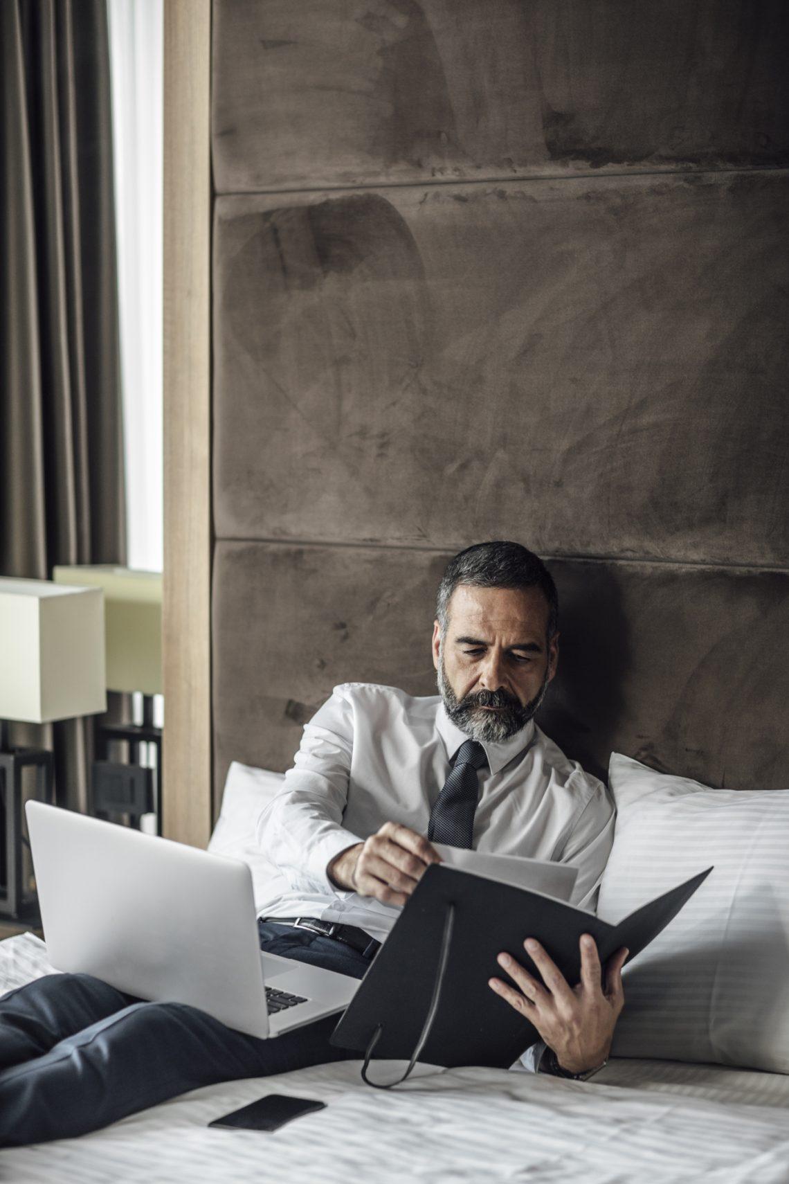 мужчина работает за ноутбуком и просматривает бумаги фото