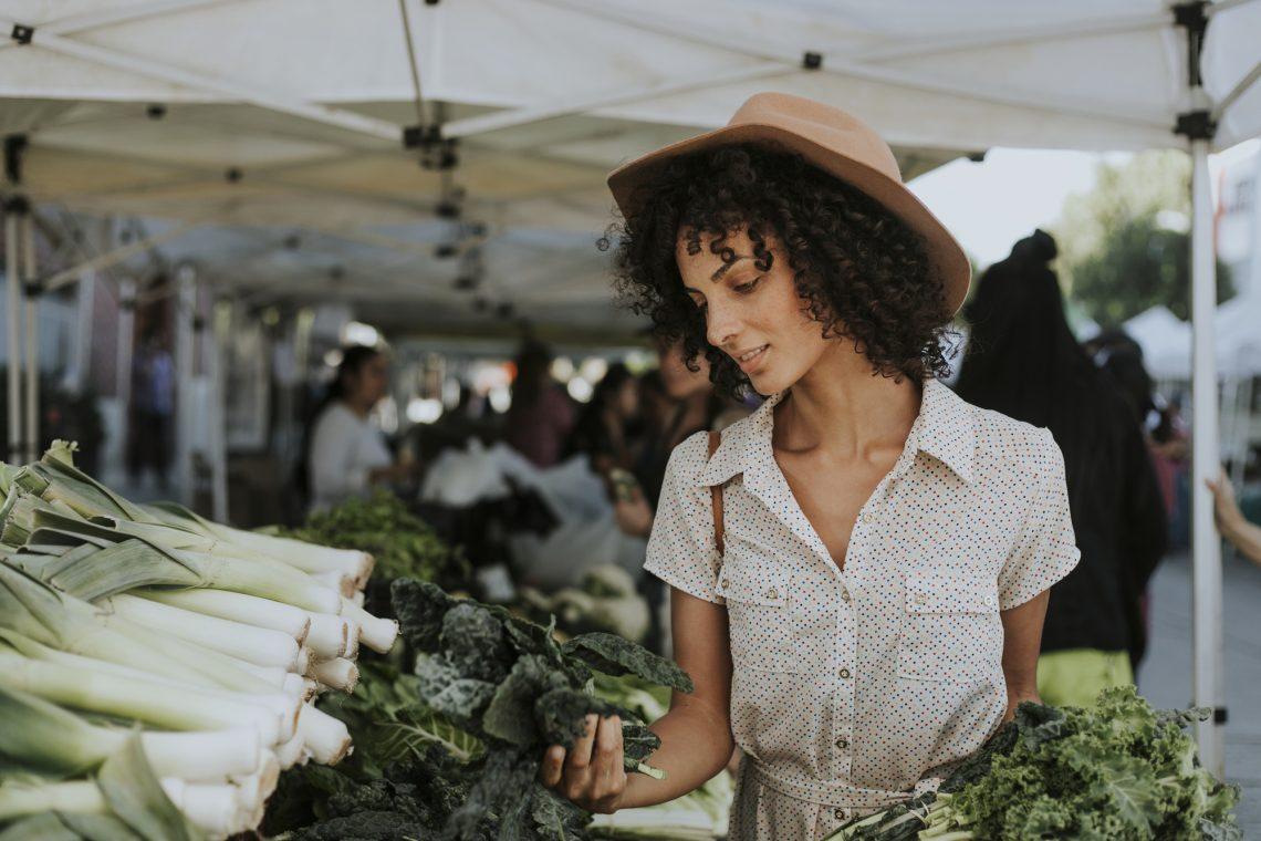 женщина выбирает овощи на рынке фото