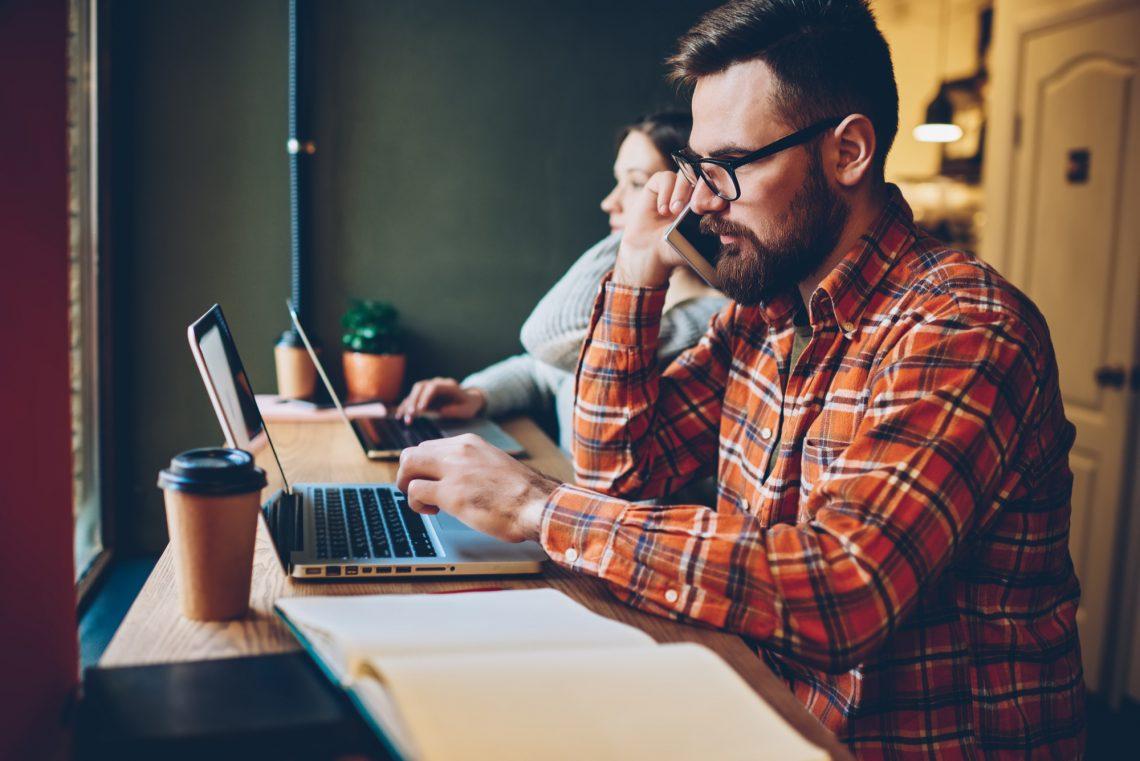 мужчина работает за ноутбуком и говорит по телефону фото