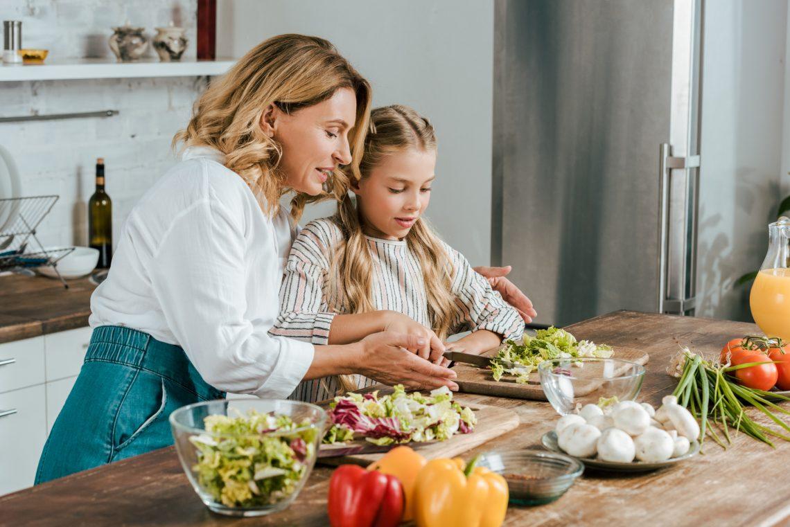 фото женщина с дочкой готовят салат на кухне