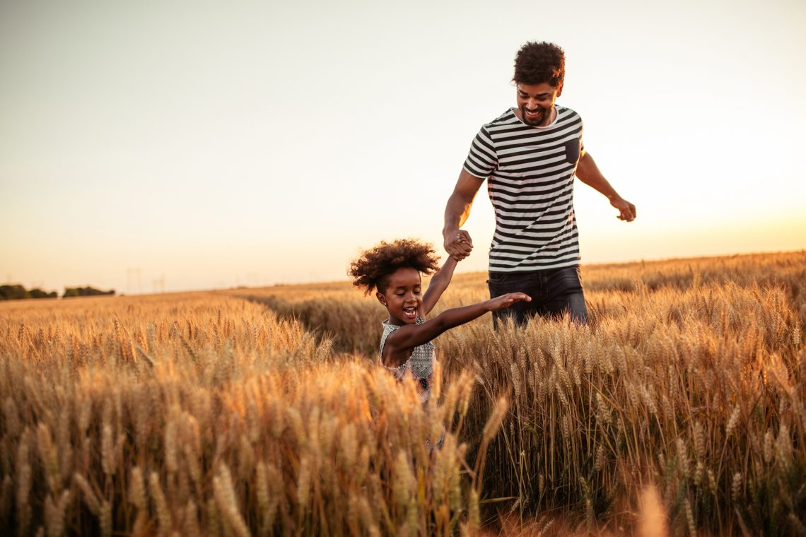 Мужчина с дочкой гуляет в поле фото