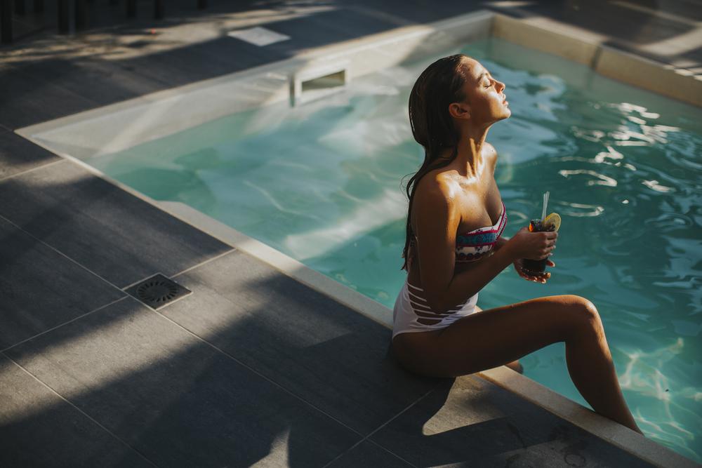 Женщина с коктейлем у бассейна фото
