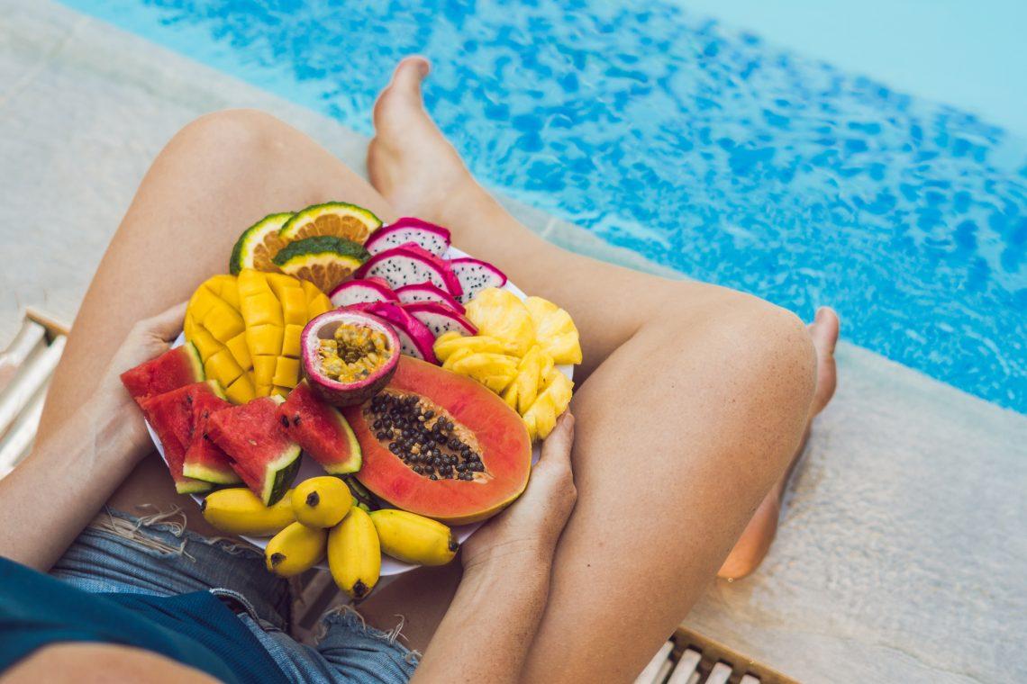 Женщина сидит с тарелкой фруктов у бассейна фото