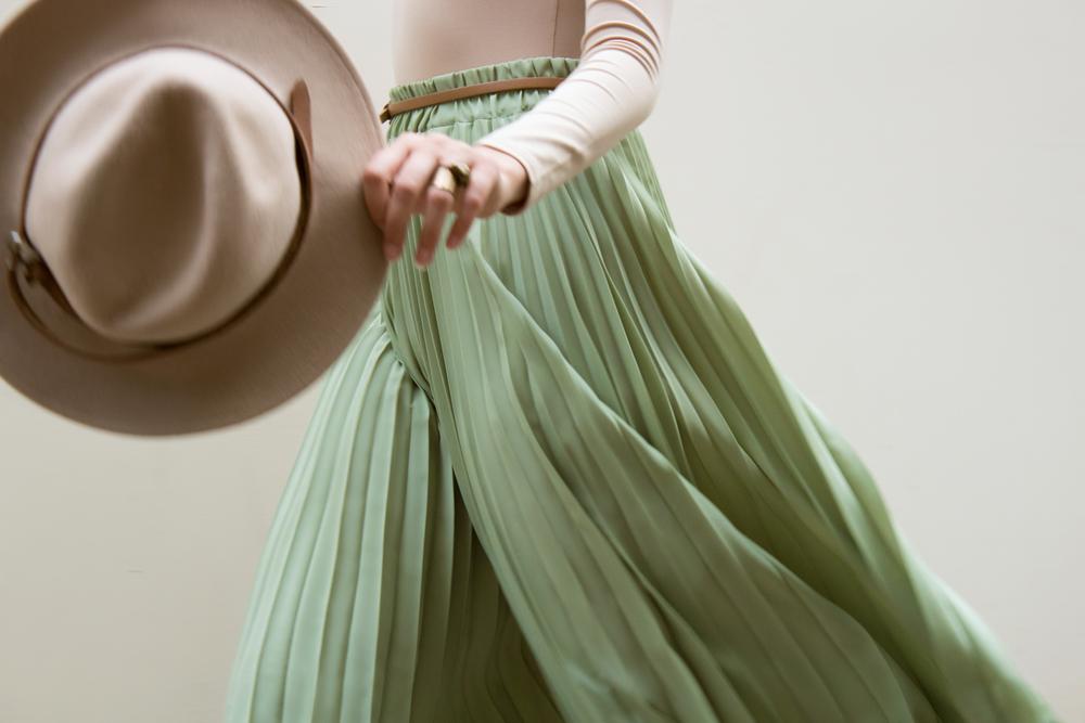 Женщина в зеленой юбке со шляпой в руках фото
