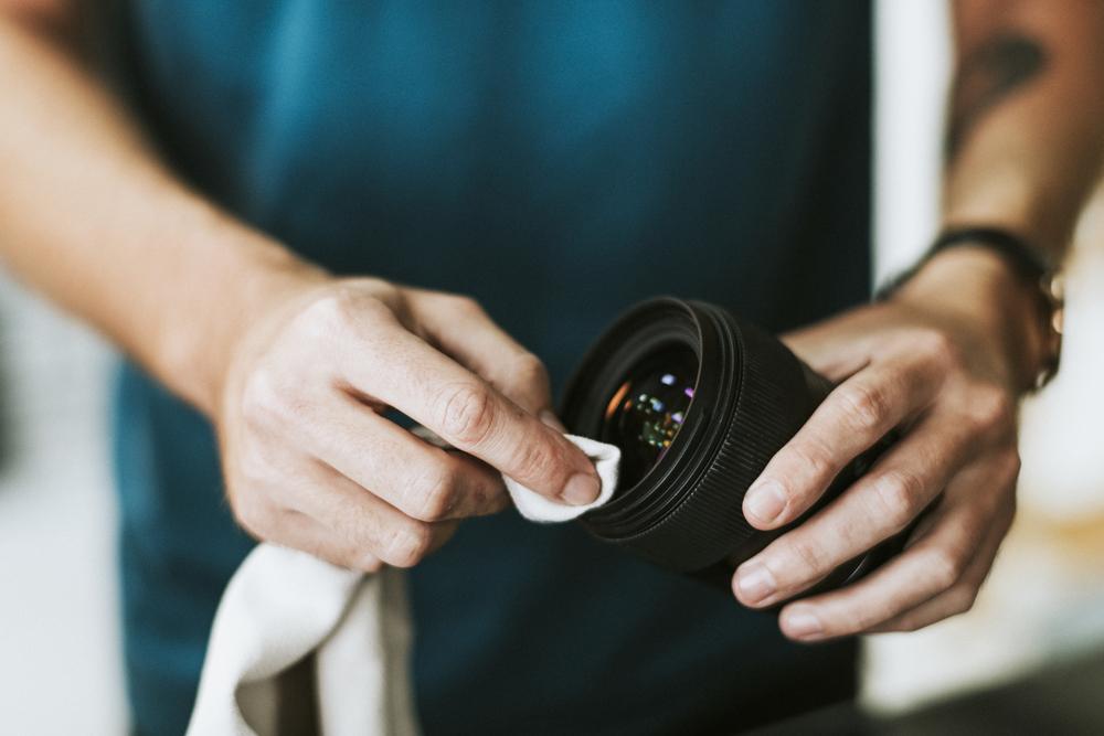 Фото фотограф чистит объектив камеры