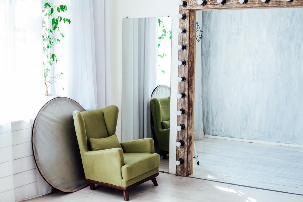 Фото зеленое кресло зеркало и отражатель в белой фотостудии