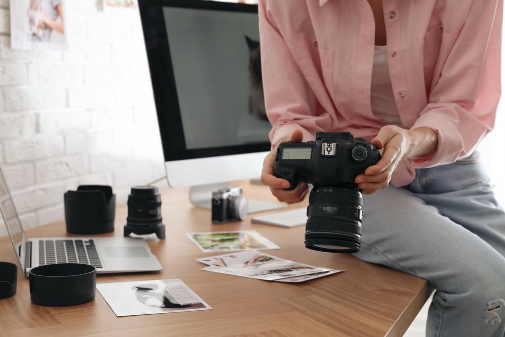 Фото женщина-фотограф с камерой сидит на столе