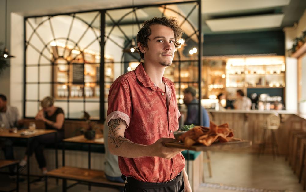 Фото молодой официант в кафе