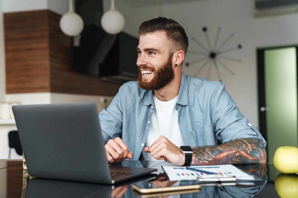 Фото молодой мужчина с бородой и татуировкой улыбается