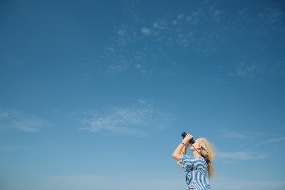 Фото женщина смотрит в бинокль на небо