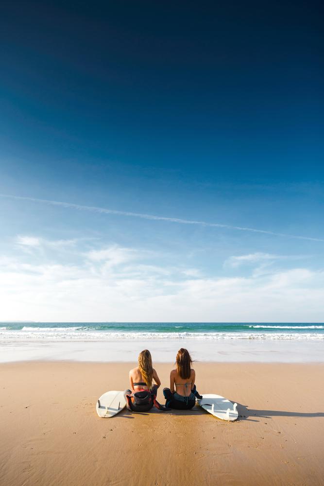 Фото две девушки серфингистки на берегу океана
