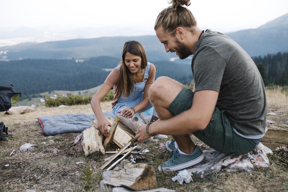 Фото мужчина и женщина в горах складывают дрова для костра