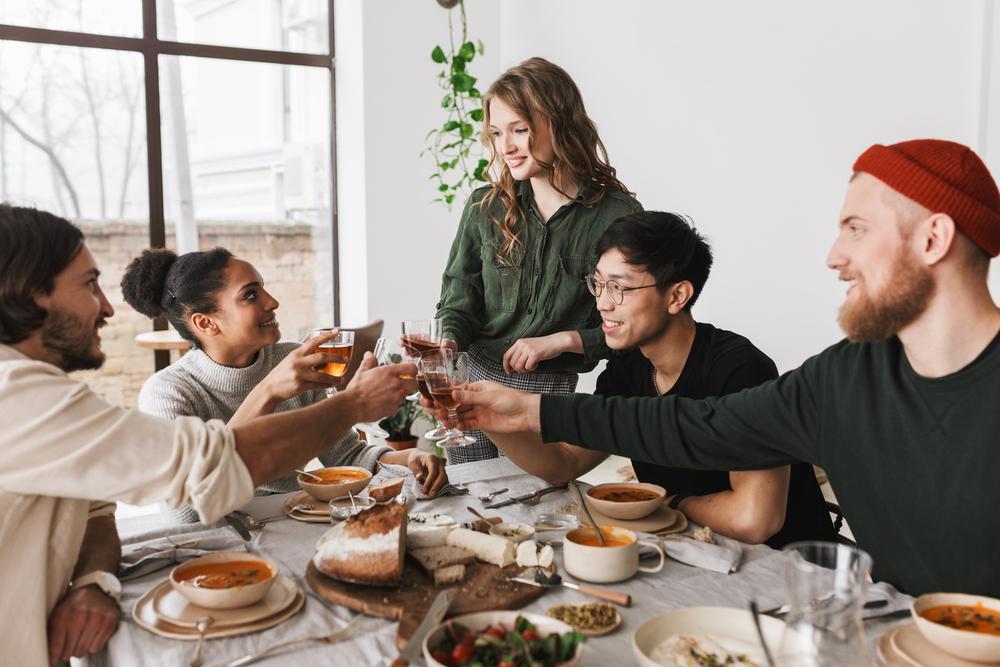 Фото компания друзей обедает за столом