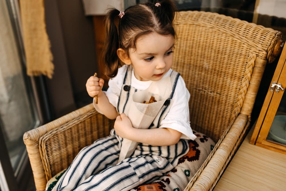 Фото дівчинка сидить на плетеному кріслі