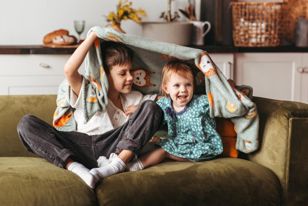 Фото хлопчик і дівчинка сидять під ковдрою