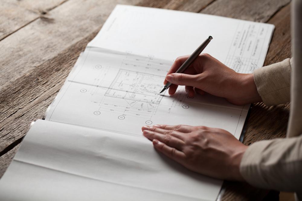 Фото женщина создает чертеж дома