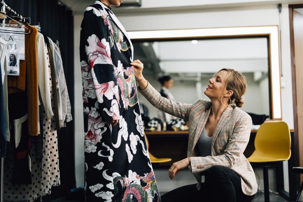 Фото женщина-дизайнер подгоняет платье