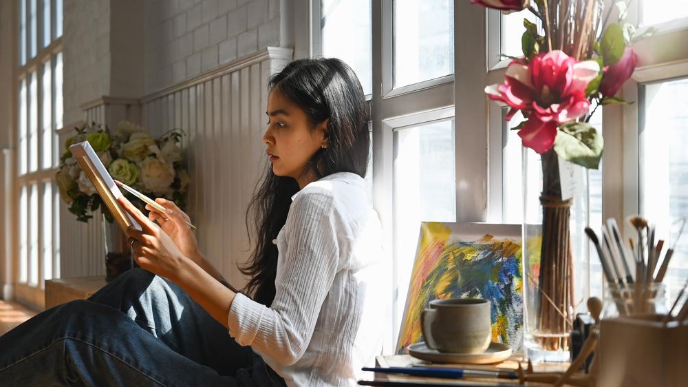 Фото девушка-художница держит картину и кисть