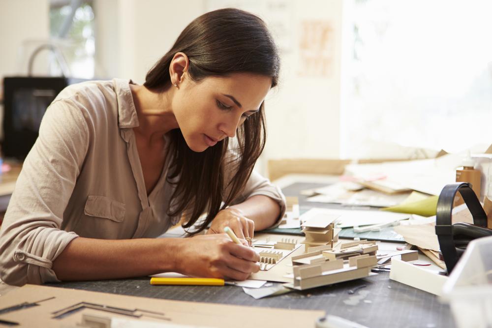 Фото женщина-архитектор создает модель здания