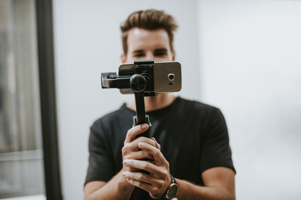 Фото мужчина держит штатив со смартфоном