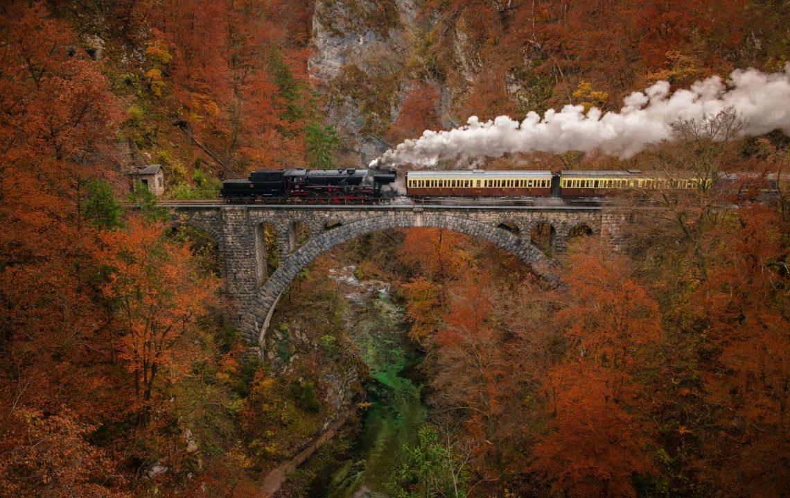 Старий поїзд переїжджає міст на фоні осінніх гір фото