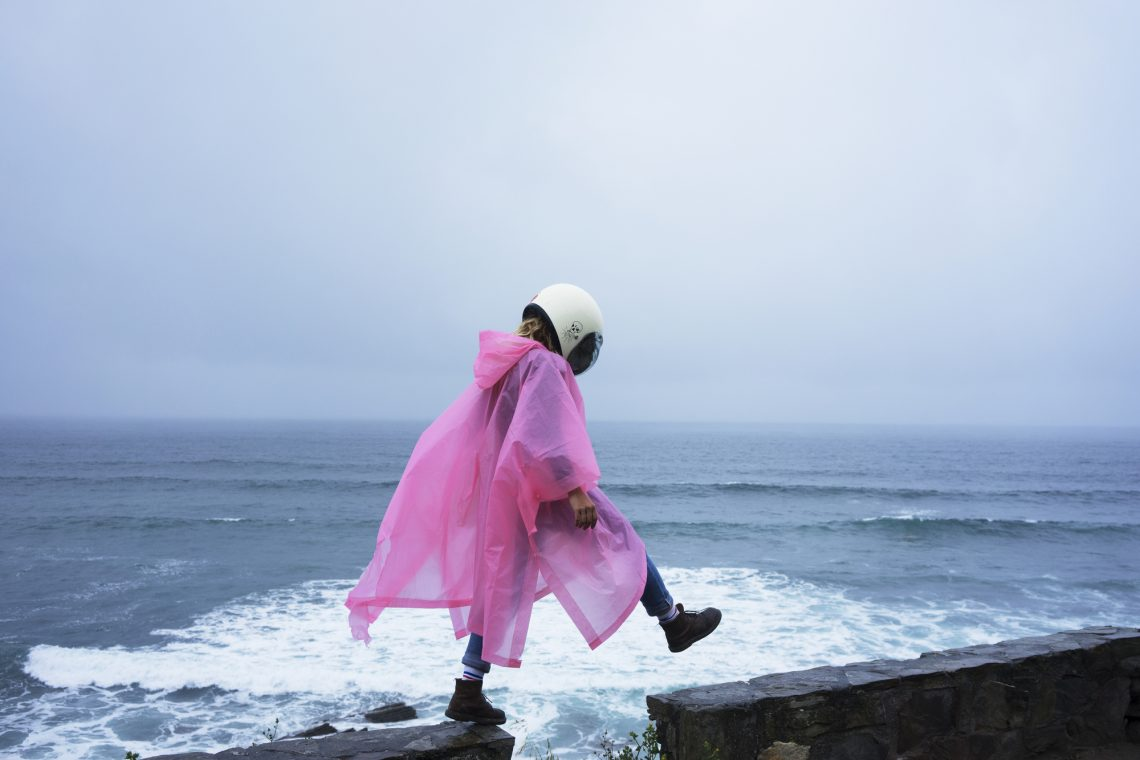 Фото дівчини у дощовику і шоломі на узбережжі