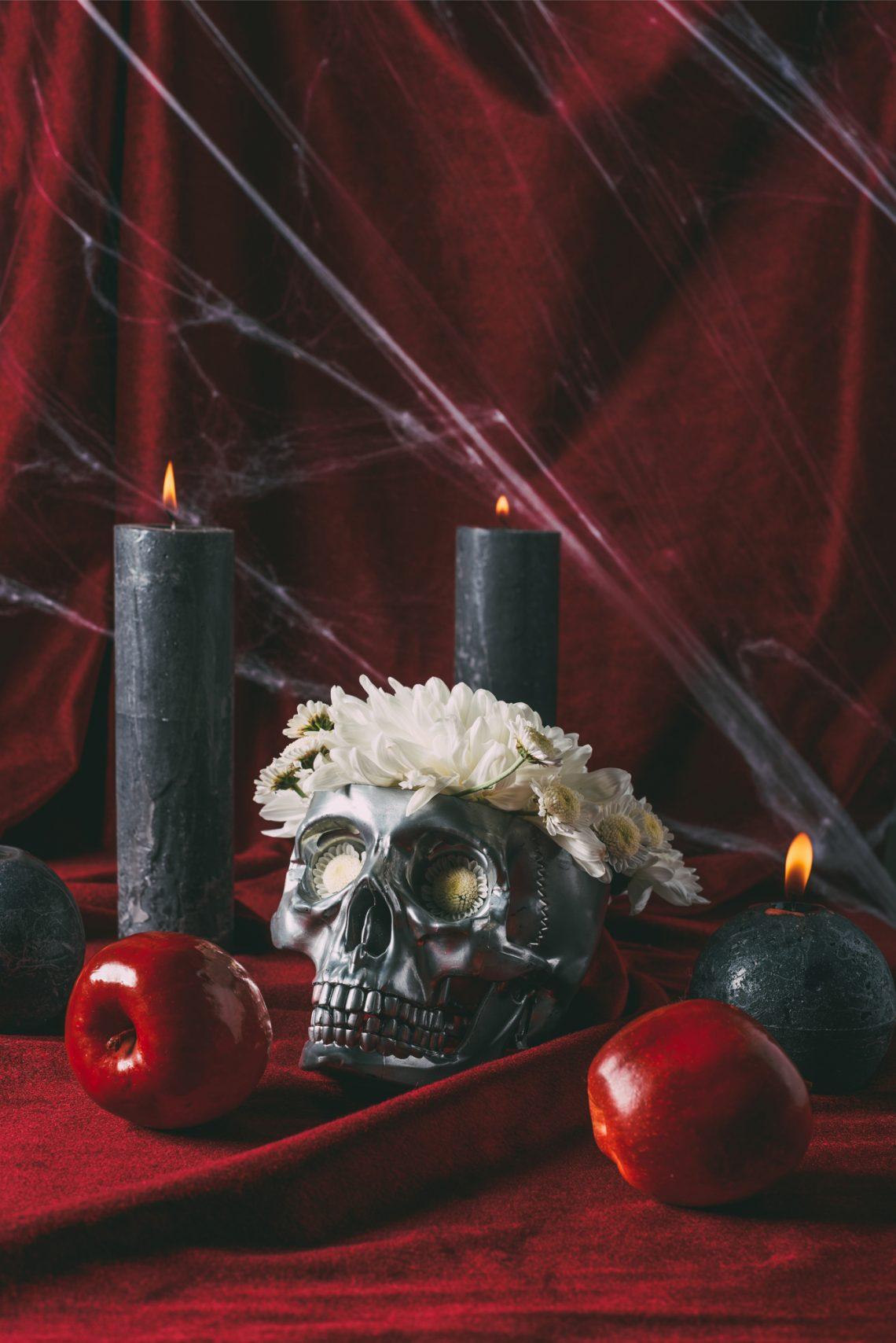 Фото черепа у вінку з чорними свічками, яблуками й павутинням