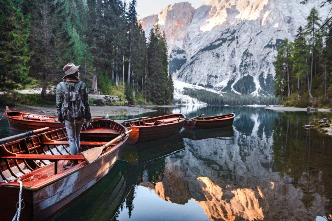 Фото мандрівниці у човні на фоні річки й засніжених гір