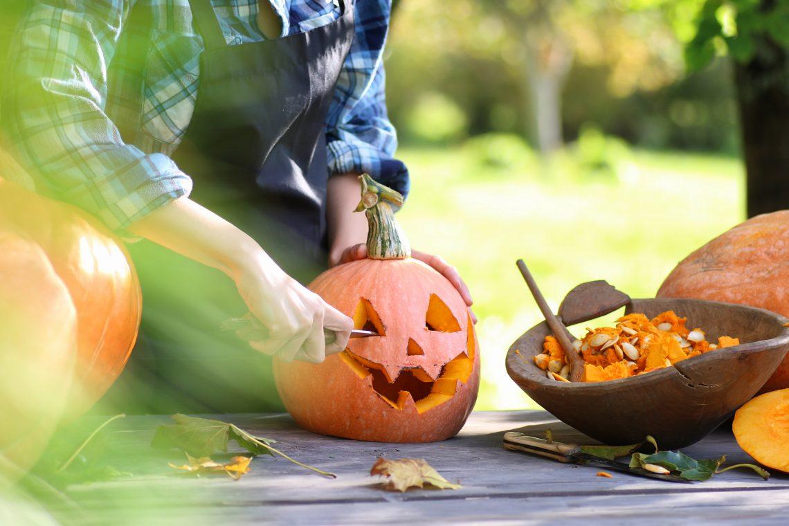 Чоловік вирізає гарбуз на Хелловін фото