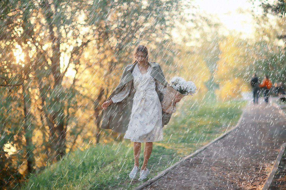 Фото дівчини у сукні і з квітами під дощем