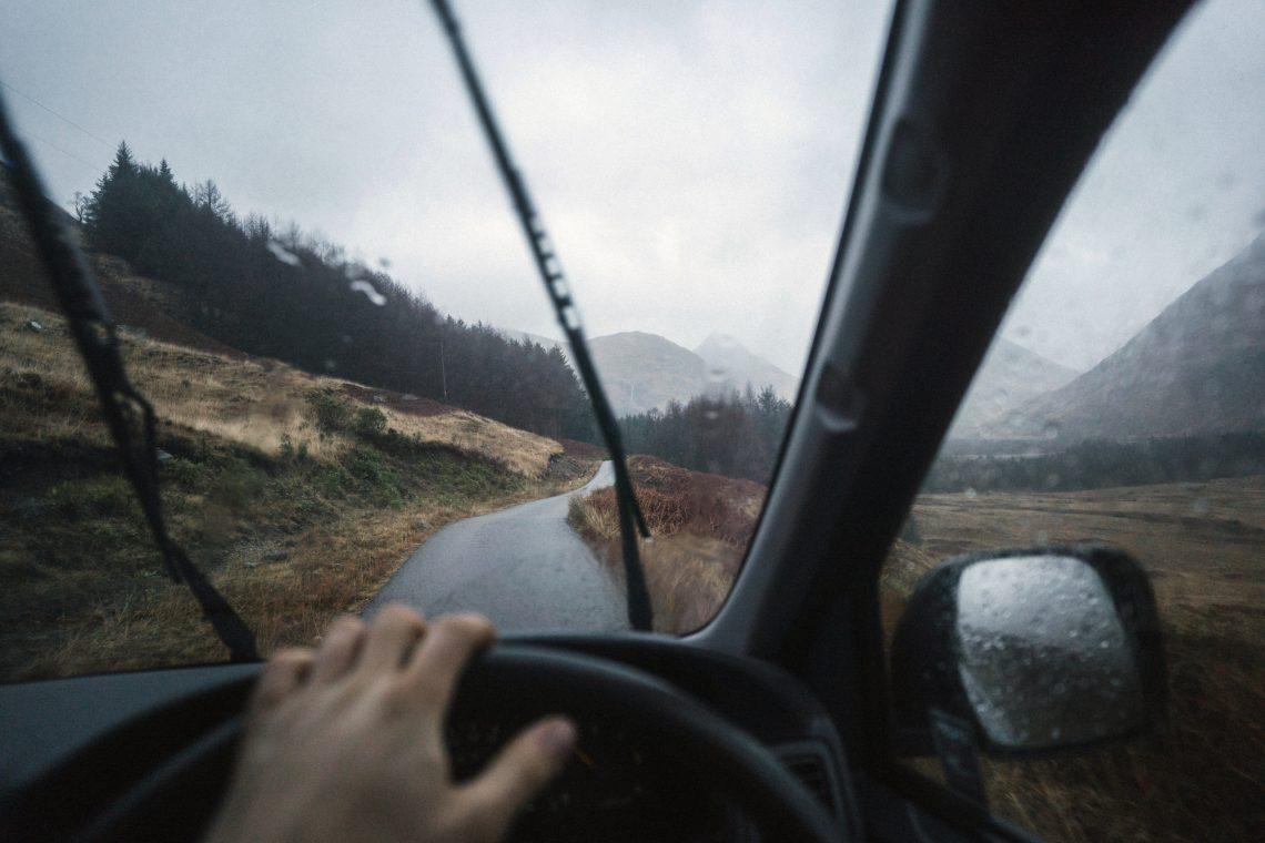 Фото чоловіка за кермом машини у дощову погоду