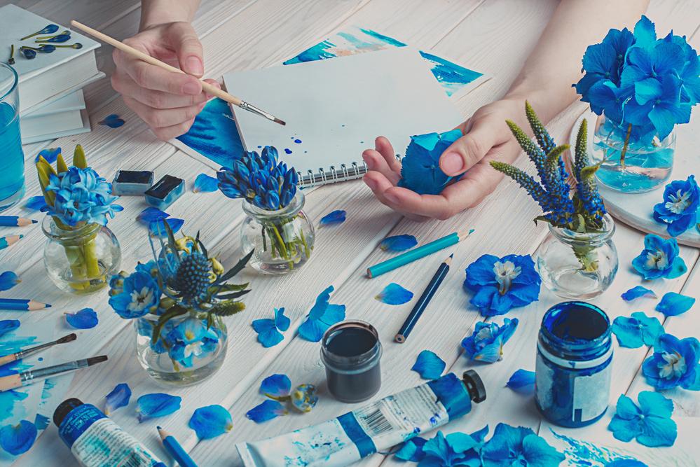 Фото руки тримають пензлик, стіл з блакитними фарбами і квітами
