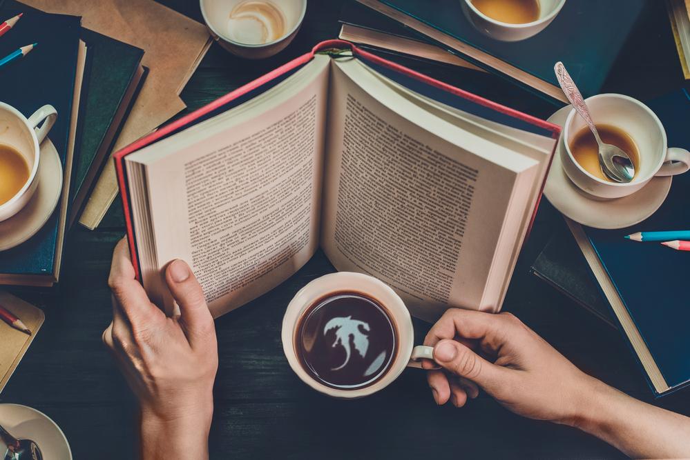 Фото руки тримають відкриту книгу і чашку кави