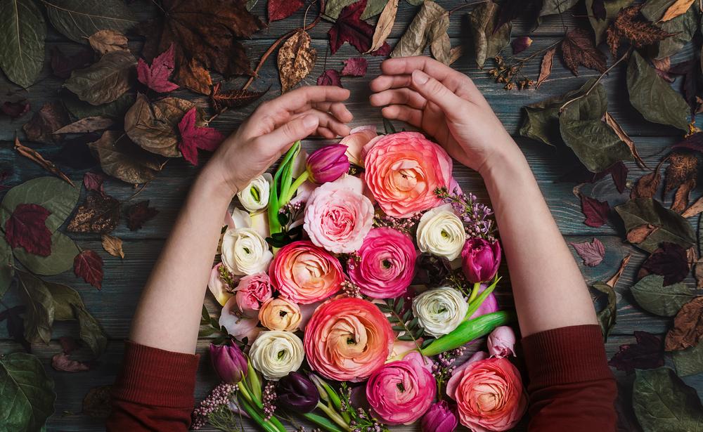 Фото руки з квітами і осіннє листя