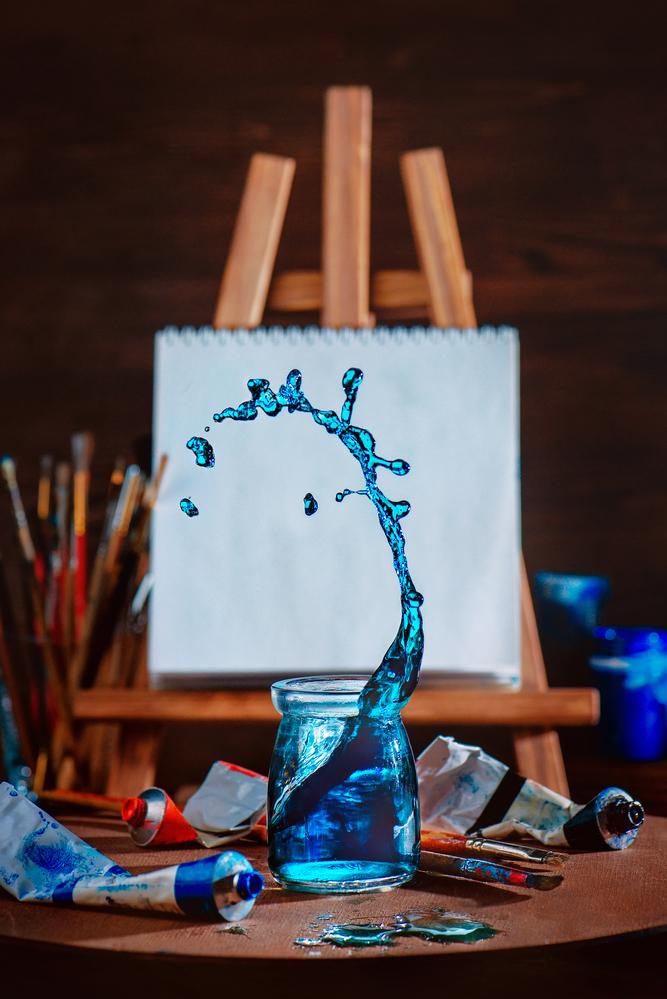 Фото склянка з водою, фарби, пензлі й мольберт