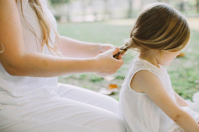 Фото жінка заплітає волосся дівчинці