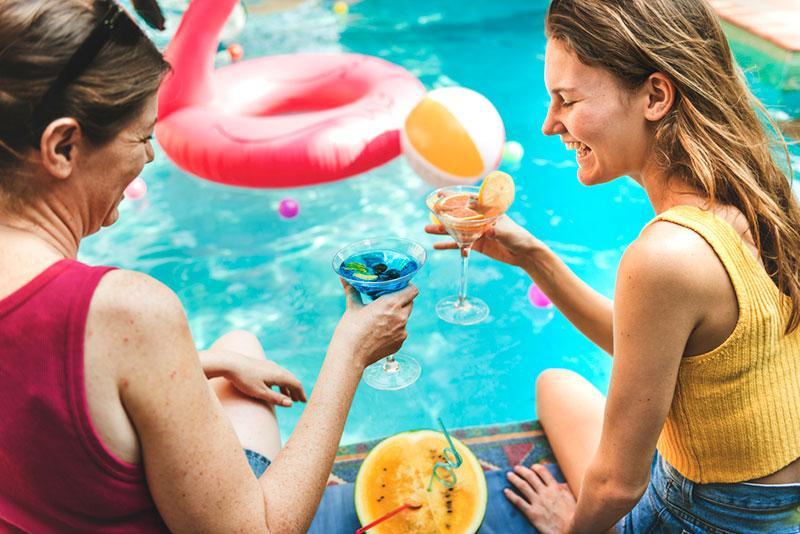Фото дівчина і жінка біля басейну з коктейлями