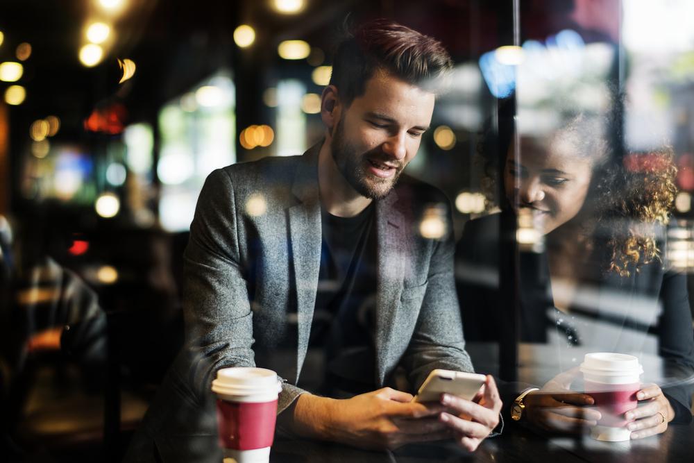 Фото чоловік і жінка у кав'ярні дивляться на екран смартфона