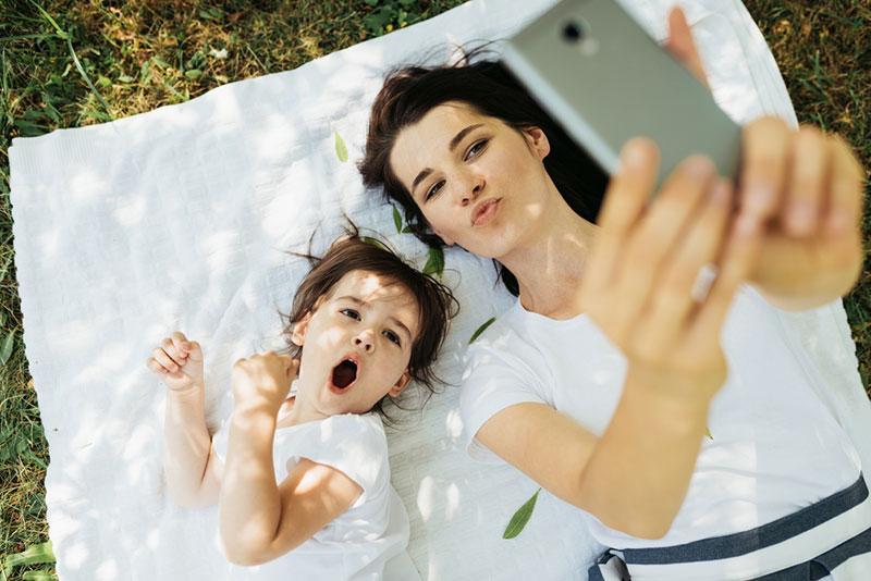 Фото жінка фотографує себе з дочкою на телефон