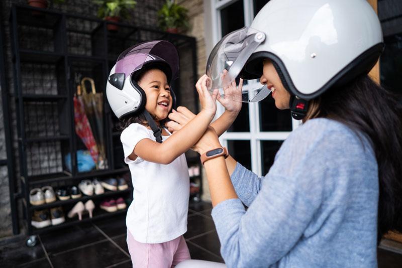 Фото дівчинка і жінка в шоломах сміються