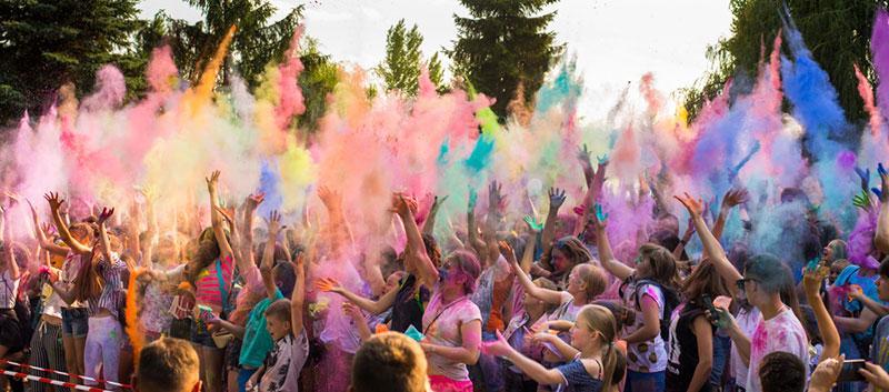 Фото люди підкидають сухі фарби вгору свято Холі