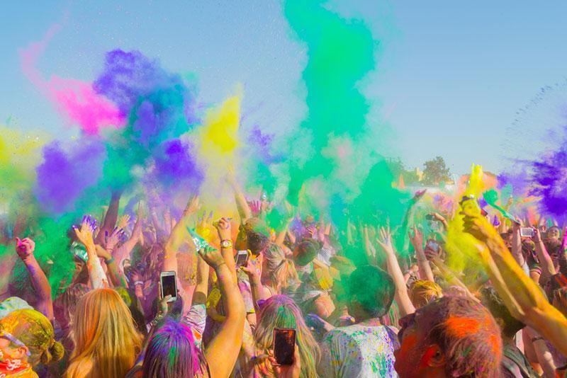 Фото люди підкидають яскраві фарби свято Холі