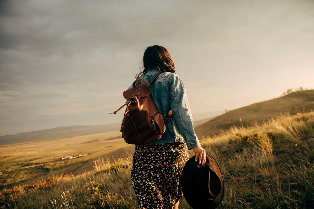 Фото дівчина з рюкзаком у полі